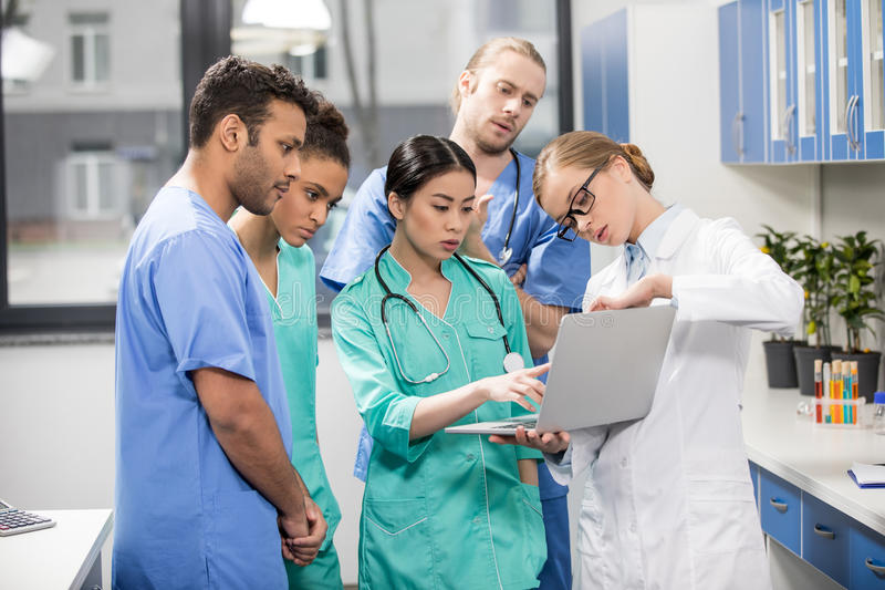 Medical workers using laptop during discussion in lab royalty free stock images