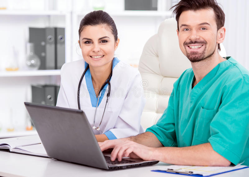 Medical. The young doctor and his assistant in a medical office at work with laptop royalty free stock photography