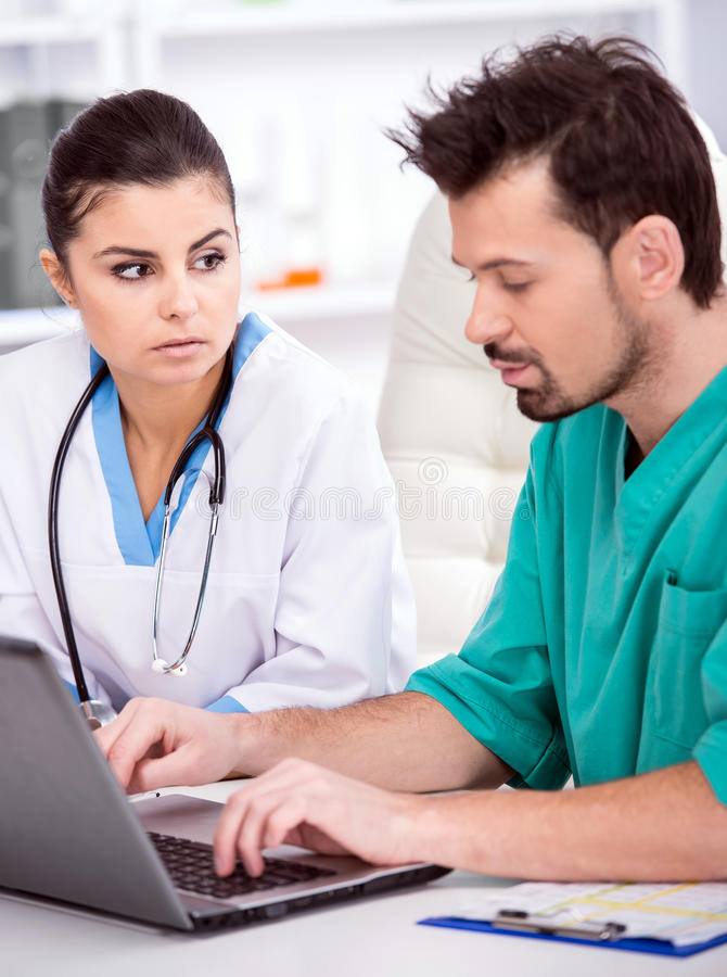 Medical. The young doctor and his assistant in a medical office at work with laptop royalty free stock photos