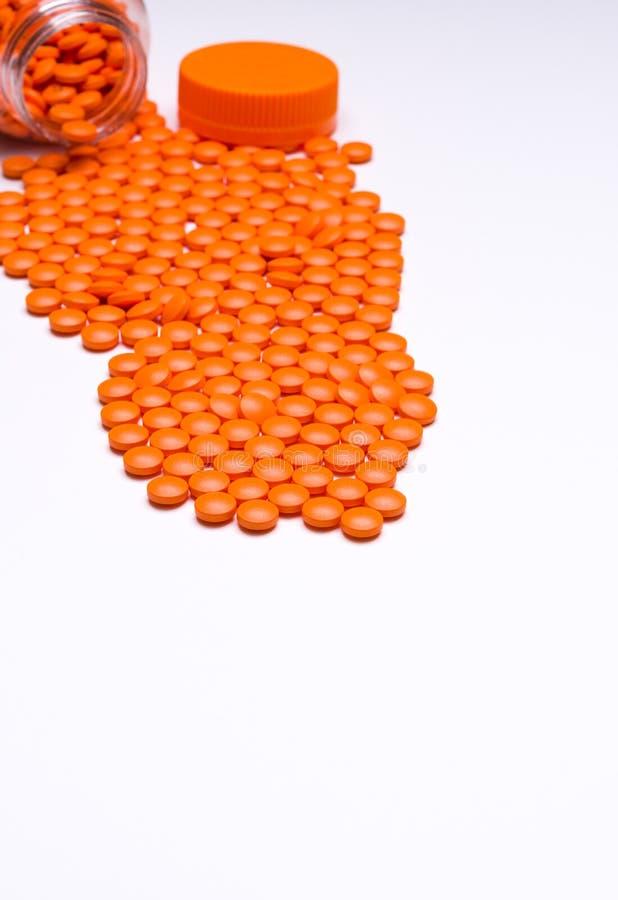 Medicamentação, comprimidos que derramam para fora em uma superfície branca fotos de stock royalty free