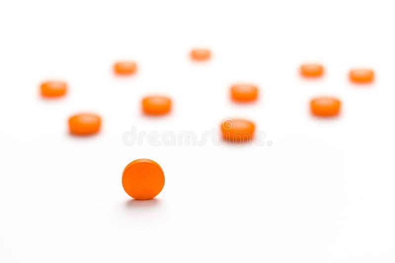 Medicamentação, comprimidos que derramam para fora em uma superfície branca imagem de stock