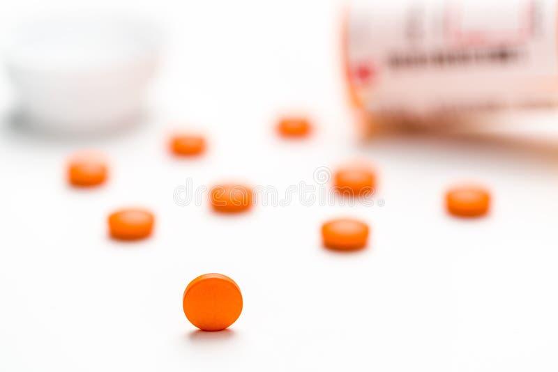 Medicamentação, comprimidos que derramam para fora em uma superfície branca fotografia de stock