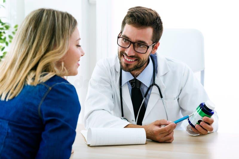 Medicamentação de prescrição do doutor masculino novo considerável para o paciente no escritório médico no hospital fotografia de stock royalty free