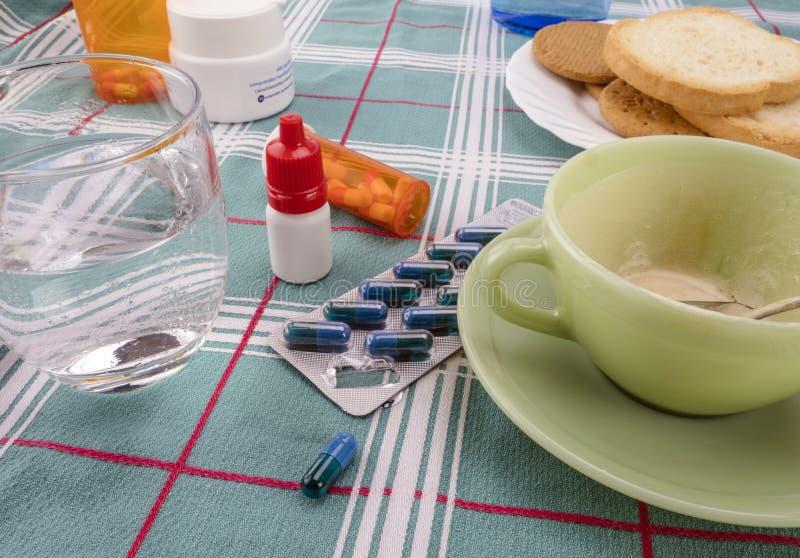 Medicamentação durante o café da manhã, cápsulas ao lado de um vidro da água, imagem conceptual imagens de stock