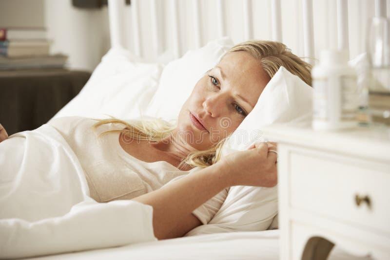 Medicamentação na tabela de cabeceira da mulher sem sono imagens de stock royalty free