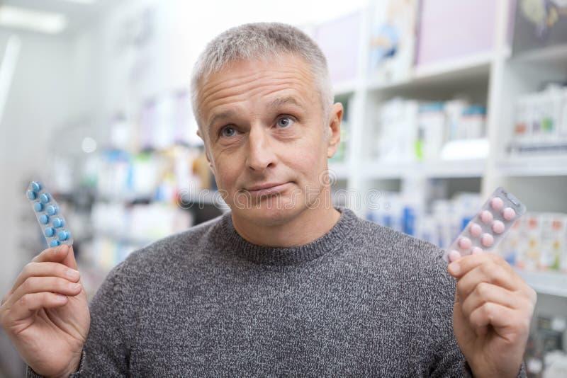 Medicamentações maduras da compra do homem na drograria imagem de stock