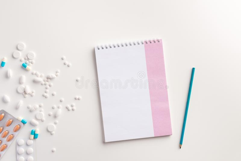 Medicaments, pencil and notebook on white background. Medical concept. Flat lay royalty free stock image