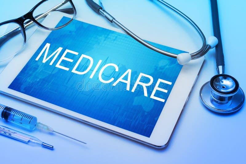 Medicare ord på minnestavlaskärmen med medicinsk utrustning arkivfoto