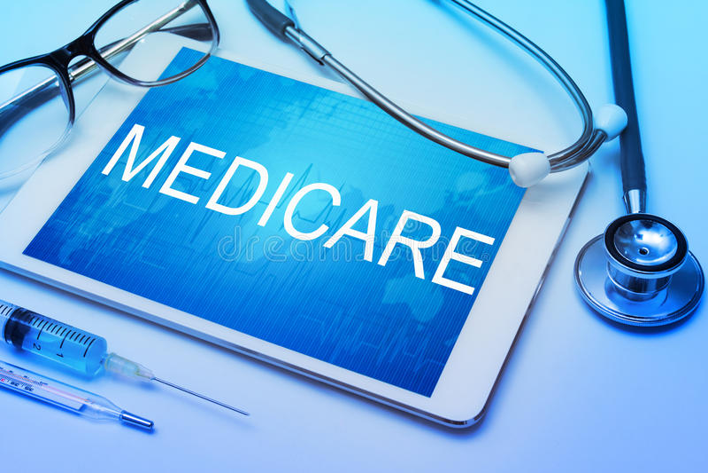 Medicare-Wort auf Tablettenschirm mit medizinischer Ausrüstung stockfoto