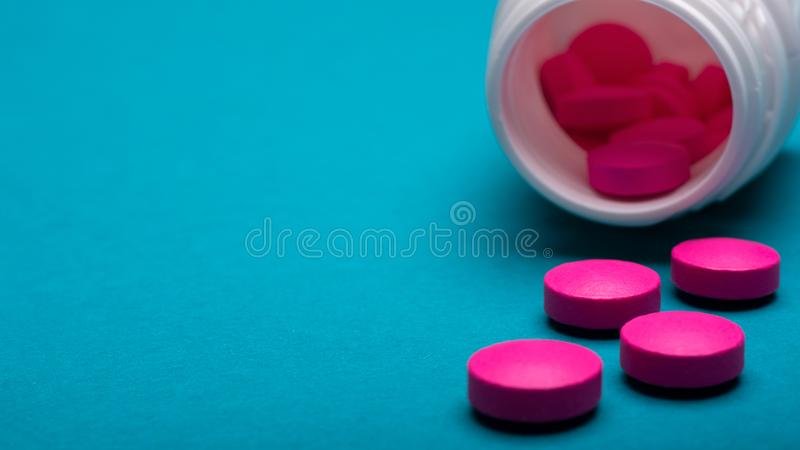Medication bottle and bright pink pills spilled on dark blue coloured background. Medication and prescription pills close up. royalty free stock photo