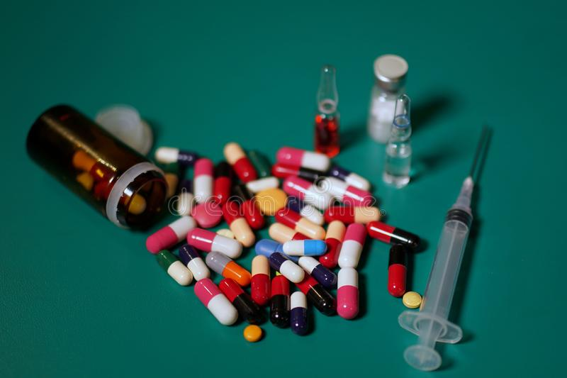 Medication capsules in an opened prescription bottle. Medicine, capsules, tablets, injection, syringe and needle. Close-up of capsules on green background stock photography