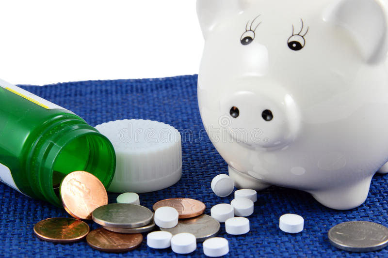 Medication Coins And Piggy Bank On Blue. A close-up photo of a piggy bank on a blue cloth with a green pill bottle, medication, and loose change. Health care stock photo