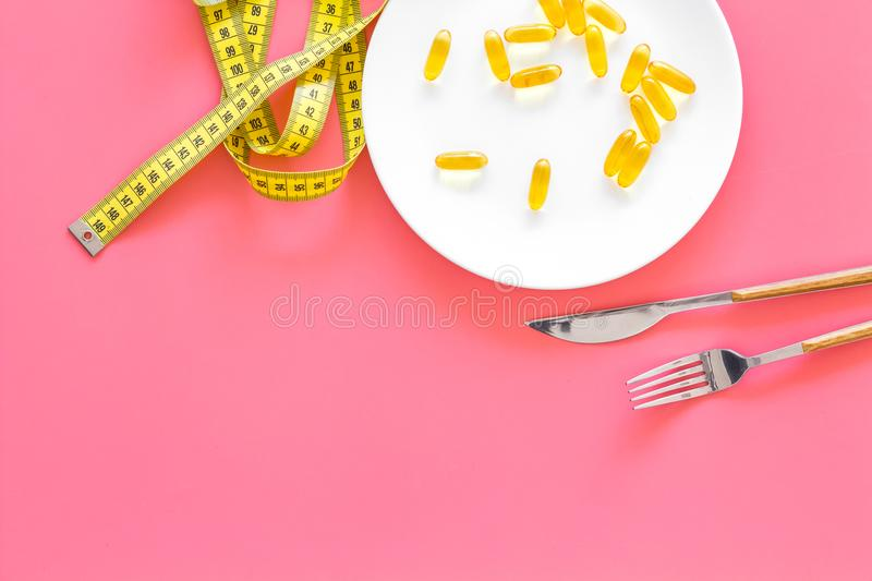 Medication and healthcare concept. Pills for treat diseases of stomach and intestines on plate near measuring tape on royalty free stock images