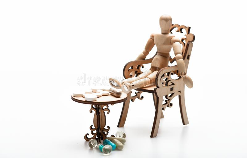 Medication regimen. Health care and medical treatment. Pills on tiny wooden table. Human wooden dummy near table with. Medicines. Tips tackling complex royalty free stock photography