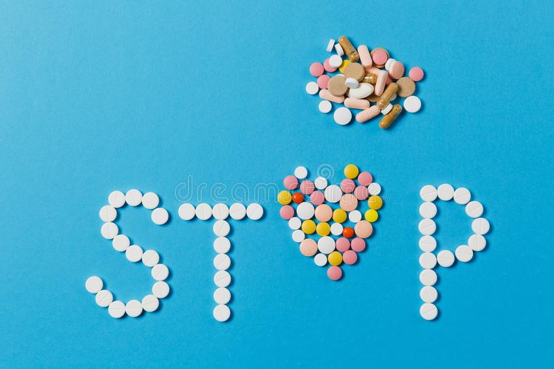 Medication tablets on color background. Concept of health, treatment, choice, healthy lifestyle. Medication white, colorful round tablets in word Stop isolated royalty free stock photography