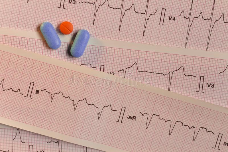 Medications in the form of tablets for oral use on an electrocardiogram background. stock photo