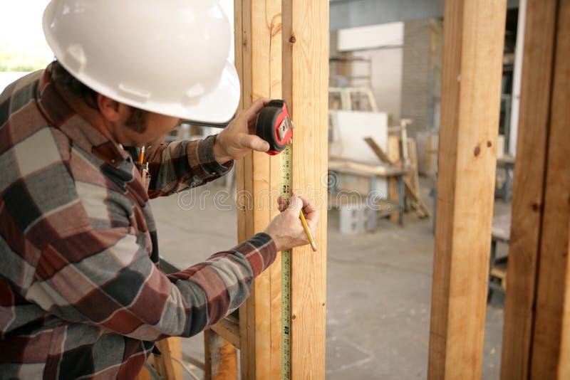 Medición del electricista de la construcción foto de archivo