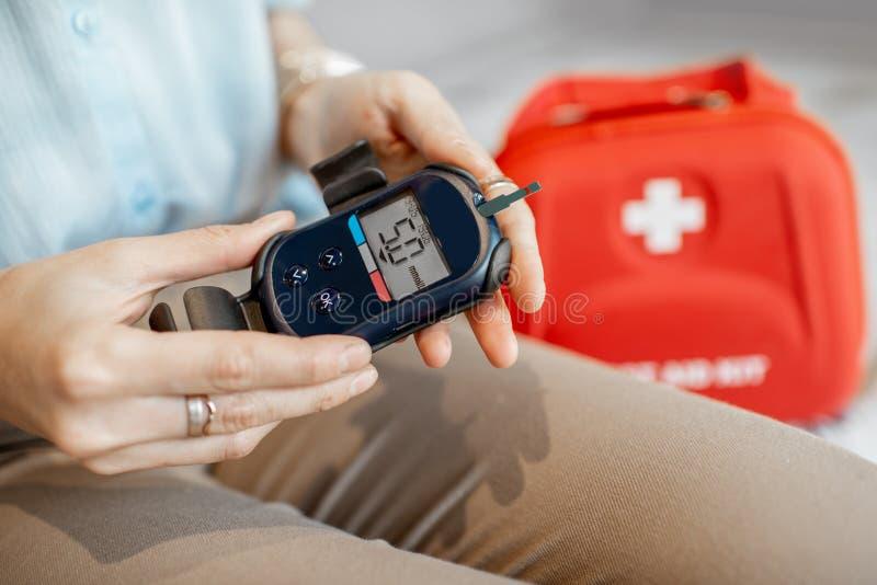 Medición del nivel de glucosa en sangre con glucometer imagen de archivo libre de regalías
