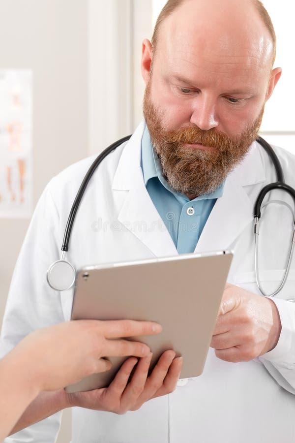 Medici che discutono rapporto circa un paziente al computer della compressa nell'ospedale fotografia stock
