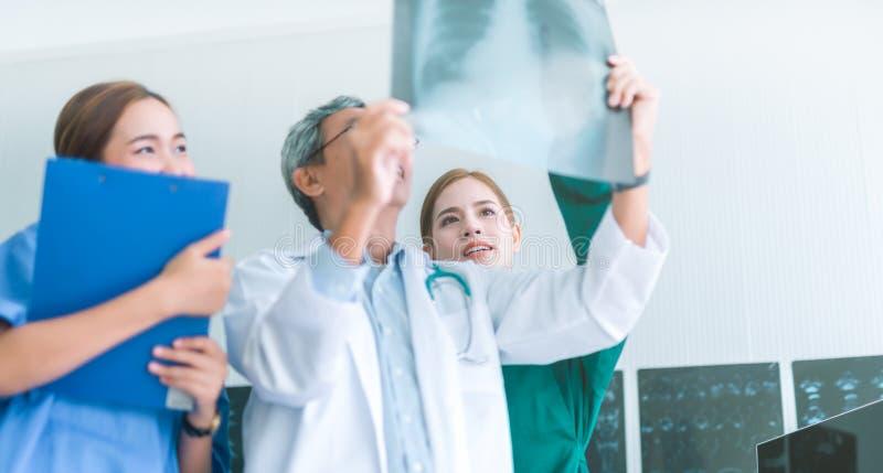 Medici che esaminano i raggi x in un ospedale controllando la lastra radioscopica del petto al reparto con l'infermiere ed il dot fotografia stock libera da diritti