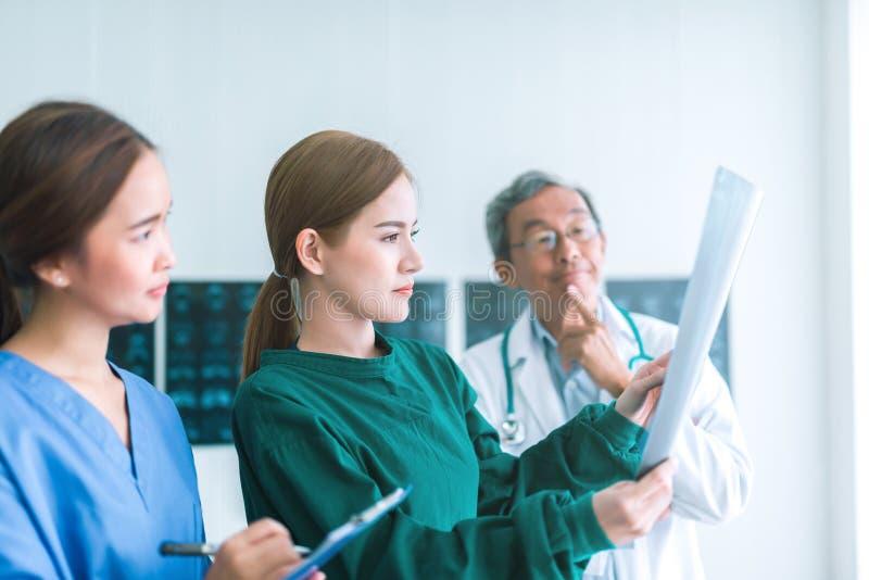 Medici che esaminano i raggi x in un ospedale controllando la lastra radioscopica del petto al reparto con l'infermiere ed il dot immagini stock