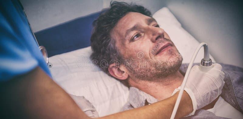 Medici che eseguono un'ecografia di doppler sul paziente immagini stock libere da diritti