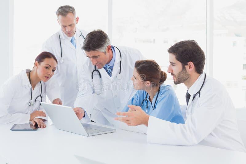 Medici che per mezzo insieme di un computer portatile immagini stock