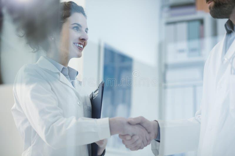 Medici che stringono le mani nell'ufficio fotografie stock