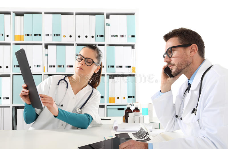 Medici con l'infermiere che sembra le cartelle sanitarie, concetto del consulti immagine stock