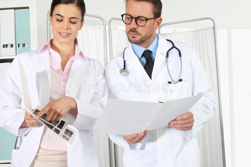 Medici con le cartelle sanitarie, concetto di si consultano immagini stock libere da diritti