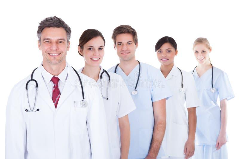 Medici ed infermiere che si levano in piedi in una riga fotografia stock