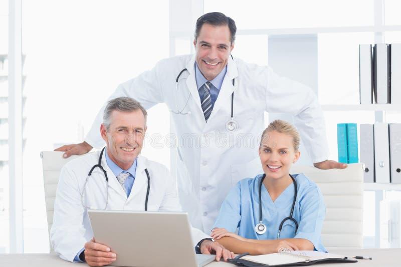 Medici ed infermiere sorridenti che esaminano macchina fotografica davanti al computer portatile fotografia stock