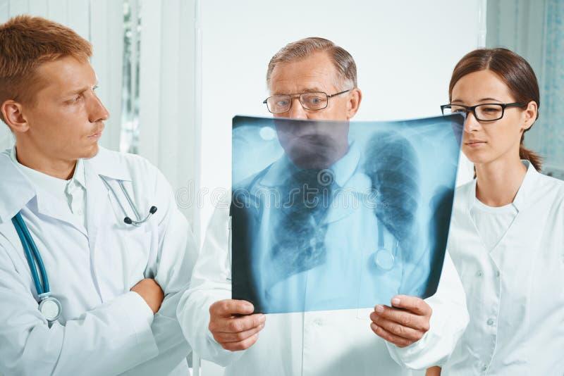 Medici esaminano l'immagine dei raggi x immagine stock libera da diritti