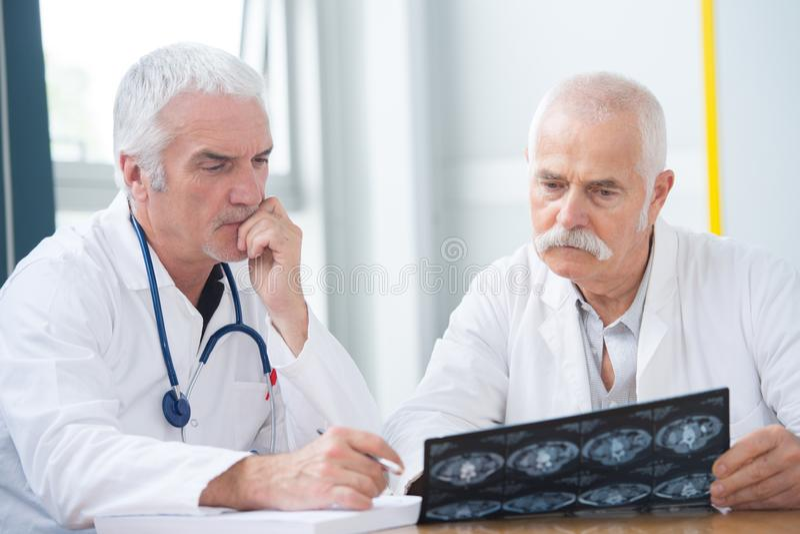 Medici infelici senior che esaminano la foto dei raggi x immagini stock