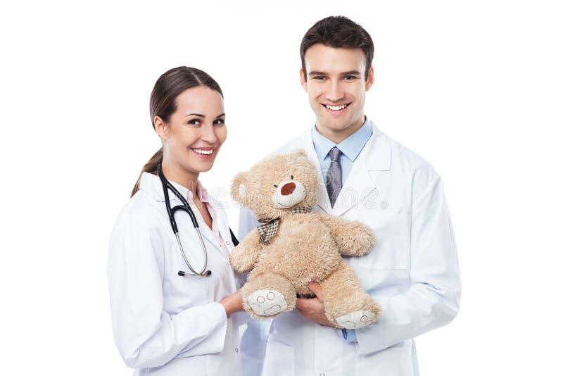 Medici pediatrici che tengono orsacchiotto immagini stock