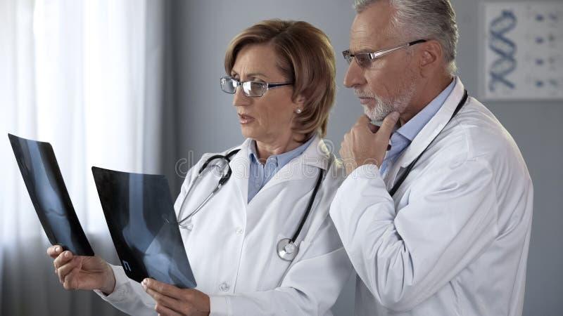 Medici responsabili circa i raggi x dei giunti risultano, discutendo i metodi di trattamento fotografia stock libera da diritti