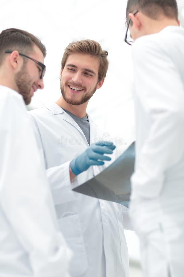 Medici sorridenti che discutono raggi x con i colleghi fotografie stock libere da diritti