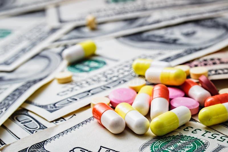 Medicina costosa El foco está en la jeringuilla Dinero y píldoras imagenes de archivo