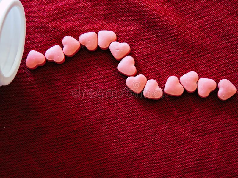 Medicina del cuore sul fondo rosso del panno Rosa rossa immagini stock