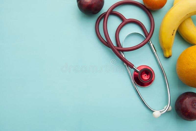 Medicina e cuidados médicos, nutrição ou seguro médico sobre o fundo azul Frutos e sthetoscop vermelho Copie o espaço fotografia de stock