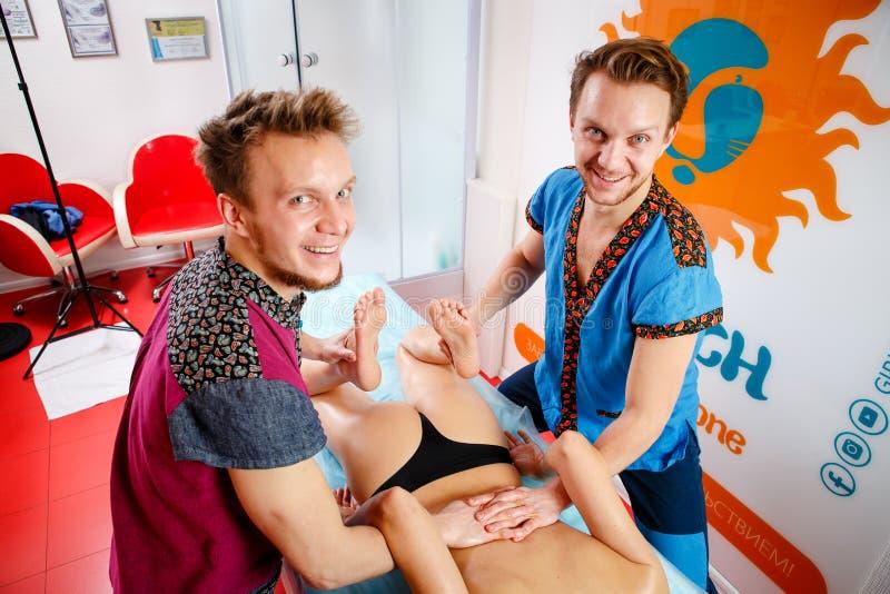Medicina e reabilitação do tema o massagista masculino novo do doutor de dois irmãos gêmeos trata a massagem de uma jovem mulher  imagem de stock