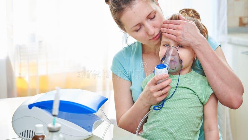 Medicina en la tabla la mujer detiene al niño, comprueba la temperatura aplicando una palma a la cabeza del niño Me siento mal fotos de archivo libres de regalías