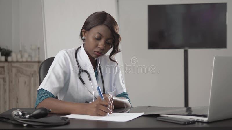 Medicina, gente y concepto de la atención sanitaria - doctor o enfermera afroamericano de sexo femenino feliz que escribe informe imagenes de archivo