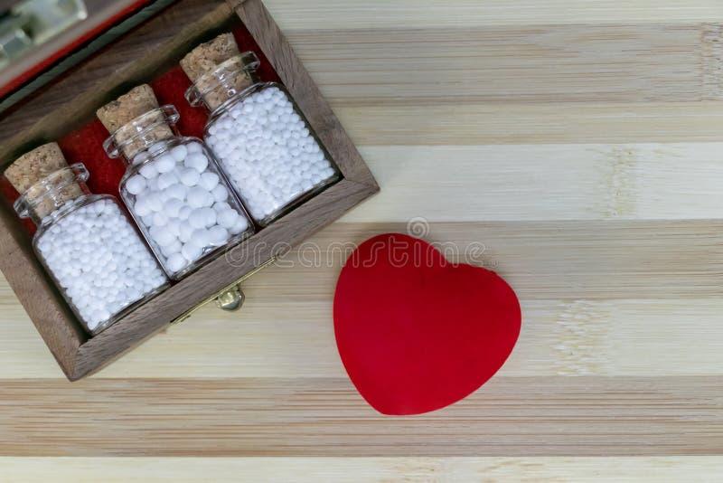 Medicina homeopática para el corazón sano - vista superior de la caja de madera vieja con las botellas de cristal homeopáticas de imagen de archivo