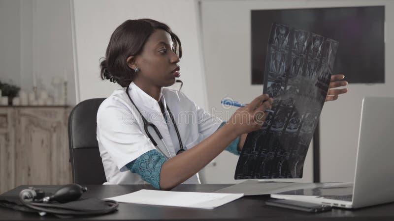 Medicina, povos e conceito dos cuidados médicos - doutor ou enfermeira afro-americano fêmea feliz que escrevem o relatório médico fotos de stock royalty free