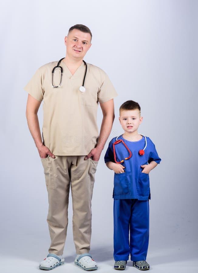 Medicina y salud ni?o feliz con el padre con el estetoscopio M?dico de cabecera padre e hijo en uniforme m?dico poco fotografía de archivo libre de regalías