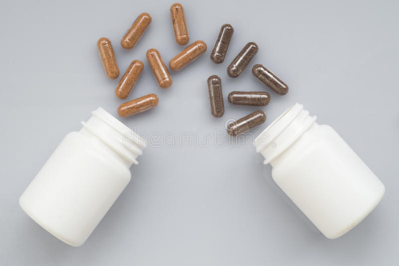 Medicinal capsule spill out of a two plastic bottles on a light. Surface stock photos