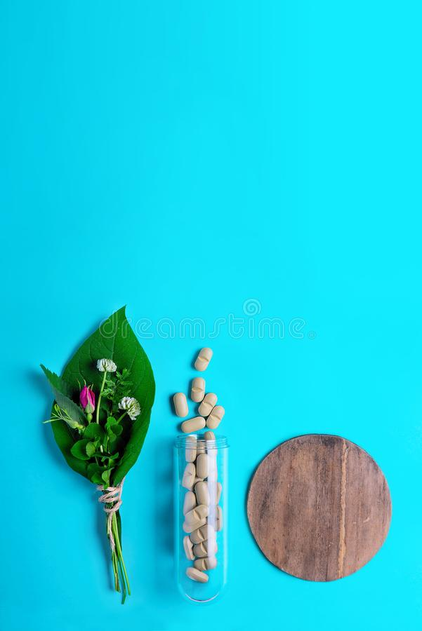 Medicinal herbs and natural tablets, bottle. The concept of the production of natural preparations and food supplements. stock photos
