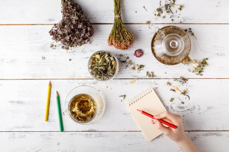 Medicinal herbs with recipe on wooden table. Flat lay royalty free stock photo