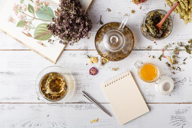 Medicinal herbs with recipe on wooden table. Flat lay stock photo